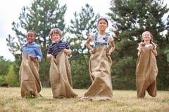 De kinderen bij zak rennen Royalty-vrije Stock Foto's