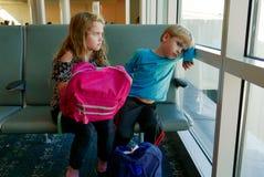 De kinderen bored bij aiport terwijl het wachten op een vlucht Royalty-vrije Stock Foto's