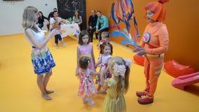 De kinderen dansen het dans` Brood ` met de animator Een vakantie in kinderen` s club stock video