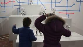 De kinderen dansen met grappige witte robots stock video