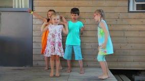 De kinderen dansen rond het huis stock videobeelden