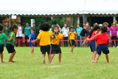 De kinderen die een groepswerk doen stellen het rennen bij de dag van de Kleuterschoolsport in werking Stock Foto's