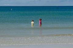 De kinderen die in het water in a waden turpuoise blauwe oceaan Stock Foto