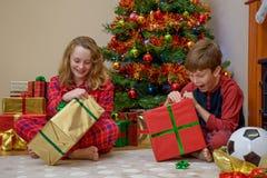 De kinderen die Kerstmis openen stelt voor Stock Foto's