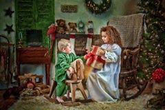 De kinderen die Kerstmis openen stelt voor stock afbeelding