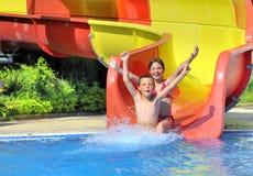 De kinderen die onderaan een water glijden glijden Stock Foto