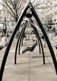 De kinderen die op een schommeling slingeren plaatsen in een stadspark op een zonnige de lentedag in sepia toon royalty-vrije stock foto's