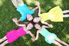 De kinderen die op het gras in de zomer liggen parkeren Stock Fotografie