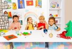 De kinderen die samen Nieuwjaarballen schilderen en zitten Stock Afbeeldingen
