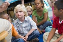 De kinderen die van de kleuterschool aan een verhaal luisteren Royalty-vrije Stock Afbeeldingen