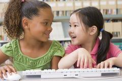De kinderen die van de kleuterschool computer met behulp van stock foto's