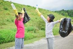 De kinderen dient het gele handschoenen verbeteren in leeg van flessenplastiek in bakzak Stock Foto's