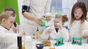 De kinderen doen een experiment in een chemieles Modern onderwijs stock footage