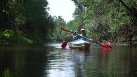 De kinderen in een kajak drijven op de rivier stock videobeelden