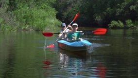 De kinderen in een kajak drijven op de rivier stock footage
