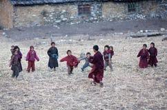 De kinderen en de monniken die van boeren voetbal spelen Royalty-vrije Stock Fotografie