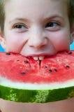 De kinderen eten watermeloenplak Stock Afbeeldingen
