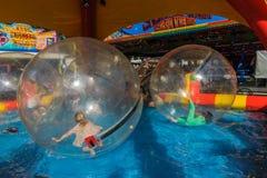 De kinderen genieten van in een luchtbal op het water in het kermisterrein stock foto's