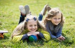 De kinderen genieten van liggend op het gras Stock Foto