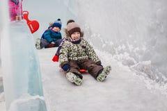 De kinderen glijden onderaan ijzige heuvel Royalty-vrije Stock Afbeeldingen
