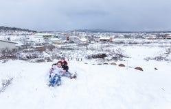 De kinderen glijden op sneeuw in oude schoolstijl met hardhout stock fotografie