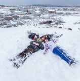 De kinderen glijden op sneeuw in oude schoolstijl met hardhout stock afbeeldingen