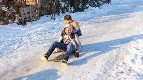 De kinderen glijden op sneeuw in oude schoolstijl met hardhout Stock Afbeelding