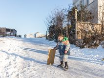 De kinderen glijden op sneeuw in oude schoolstijl met hardhout royalty-vrije stock afbeelding