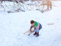 De kinderen glijden op sneeuw in oude schoolstijl met hardhout Royalty-vrije Stock Afbeeldingen