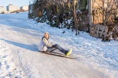 De kinderen glijden op sneeuw in oude schoolstijl met hardhout Royalty-vrije Stock Fotografie