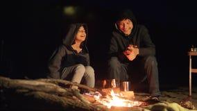 De kinderen glimlachen jonge geitjes drinken theetiener zitten door de brand bij nachtkampvuur reis het avontuur van de wandeling stock video