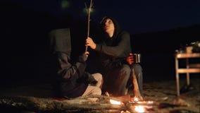De kinderen glimlachen jonge geitjes drinken theetiener zitten door de brand bij nachtkampvuur reis wandelingsavontuur het kamper stock videobeelden