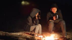 De kinderen glimlachen jonge geitjes drinken theetiener zitten door de brand bij nachtkampvuur reis wandelingsavontuur het kamper stock video
