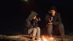 De kinderen glimlachen jonge geitjes drinken theetiener zitten door de brand bij nachtkampvuur reis wandelingsavontuur het kamper stock footage