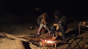 De kinderen glimlachen jonge geitjes drinken theetiener zitten door levensstijl de brand bij nachtkampvuur reis wandelingsavontuu stock footage