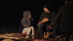 De kinderen glimlachen jonge geitjestiener zitten door de brand bij nachtkampvuur reis wandelingsavontuur het kamperen avontuur h stock footage