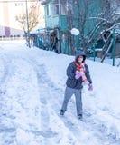 De kinderen hebben pret op sneeuw in de winter Stock Afbeelding