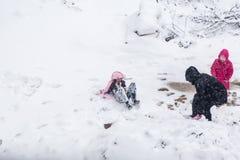 De kinderen hebben pret op sneeuw in de winter royalty-vrije stock afbeelding