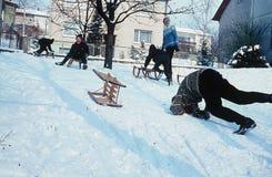 1964: De kinderen hebben pret terwijl het tobogganing in de winter duitsland stock fotografie