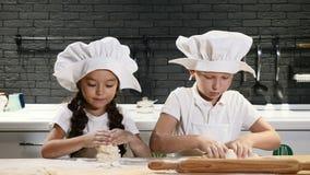 De kinderen hebben pret terwijl samen het koken Jong geitjekeuken De jonge geitjes zijn in het spel van chef-kokhoeden met deeg 4 stock video