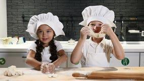 De kinderen hebben pret terwijl samen het koken Jong geitjekeuken De jonge geitjes zijn in het spel van chef-kokhoeden met deeg 4 stock videobeelden