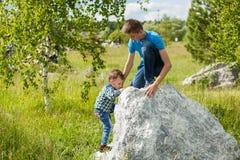 De kinderen helpen elkaar om de rots te beklimmen royalty-vrije stock foto's