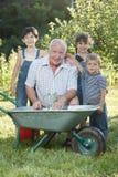 De kinderen helpt haar Grootvader in de tuin Royalty-vrije Stock Foto's