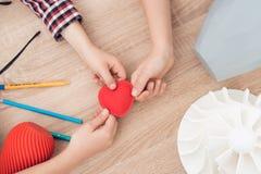 De kinderen houden een rood die hart op een 3d printer wordt gedrukt Royalty-vrije Stock Foto's
