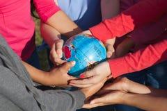 De kinderen houden globus Stock Foto's