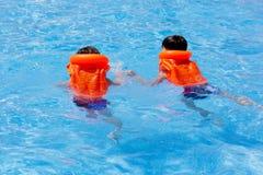 De kinderen, 2 jongens in reddingsjasje zwemmen in het water Pool stock foto