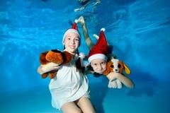 De kinderen in kappen van Santa Claus zwemmen en spelen onderwater in de pool, die een stuk speelgoed hond houden, bekijkend de c stock foto's