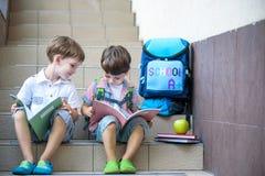 De kinderen keren naar school terug Begin van nieuw schooljaar na de zomervakantie Twee Jongensvrienden met rugzak en boeken op e stock afbeeldingen