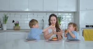 De kinderen in de keuken voeden hun mamma met zelf-gekookte dieetburgers stock videobeelden