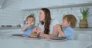 De kinderen in de keuken voeden hun mamma met zelf-gekookte dieetburgers stock footage